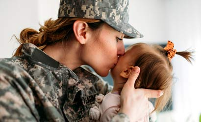 Mom in a military uniform kissing her baby