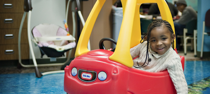 A patient rides a Little Tykes car in the Cancer and Blood Disorders Center at CHKD