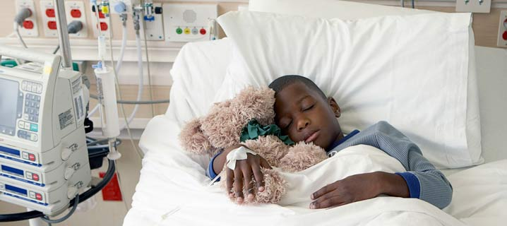 Child in a hospital bed holding a teddy bear