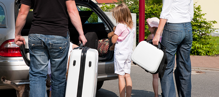 A family packs their car for a road trip.