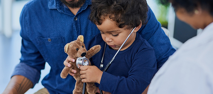 Child uses doctor's stethoscope to check teddy bear's heart