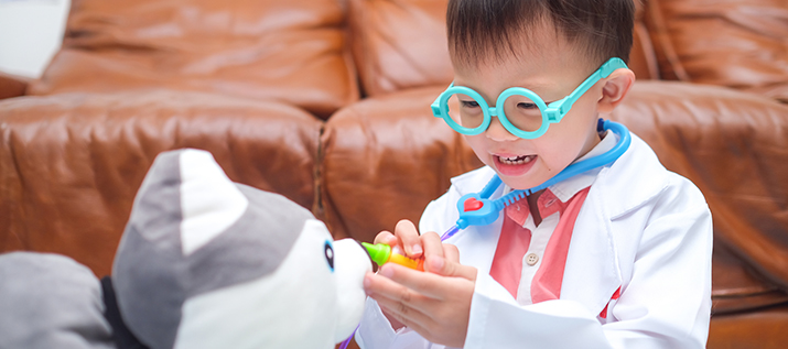 3 - 4 year old toddler boy in doctor uniform playing doctor with plush toy at home