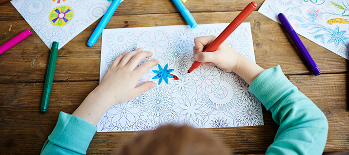 Close up of a child coloring flowers with markers