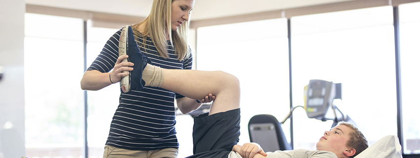 Physical therapist helping patient do knee exercise