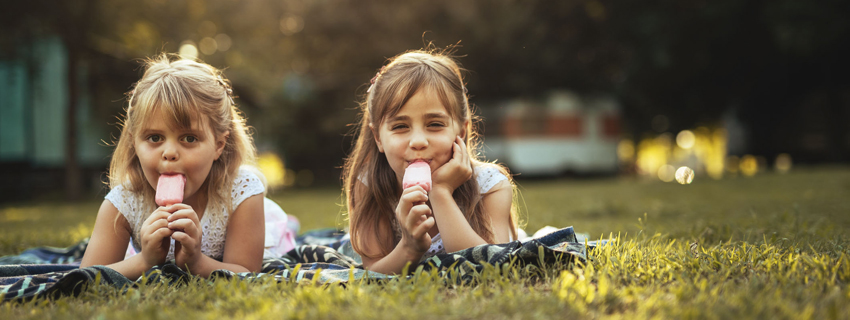 Two young children enjoying ice cream outside