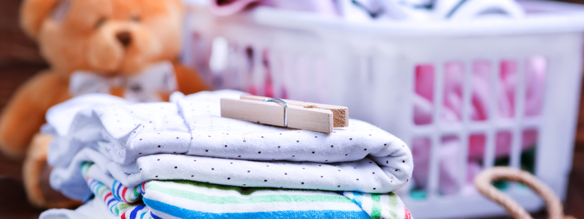 Close up of a baby clothes with laundry basket in the background