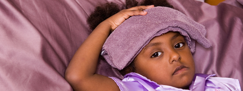 Close up of a child with a washcloth on her head