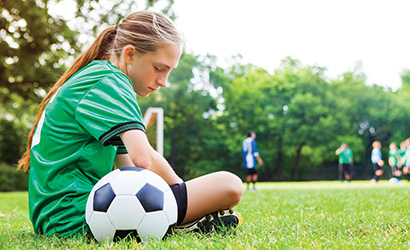 Young girl looking sad on the soccer field