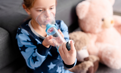 Child using inhaler with spacer
