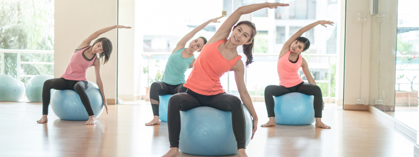 Teenage girls on exercise balls doing Pilates
