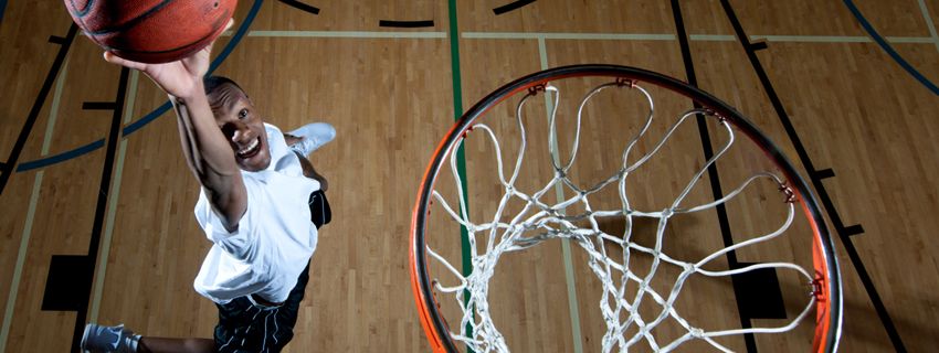 Teen athlete about to dunk a ball, photo taken from above the net