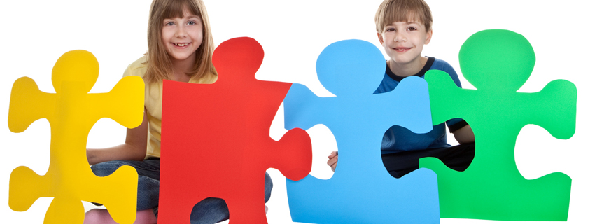 Two children holding large puzzle pieces