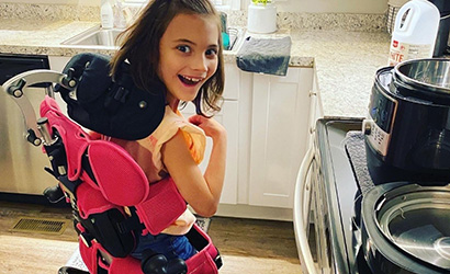 Macie Leiphart, 7, enjoys a higher view in the family kitchen in Virginia Beach, thanks to an adaptive device that helps her stand.