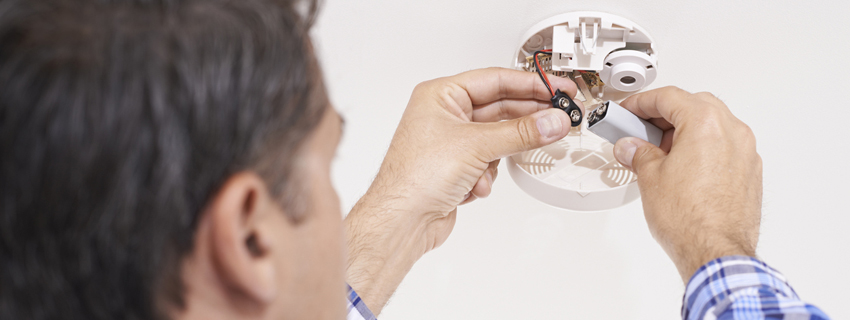 Man changing the battery in a smoke detector