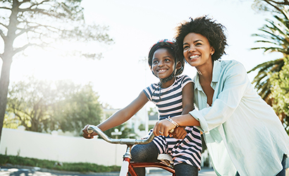 Mother showing her daughter how to ride a bike.