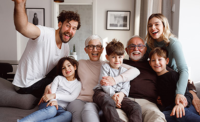 A multi-generational family is posting in front of the camera.