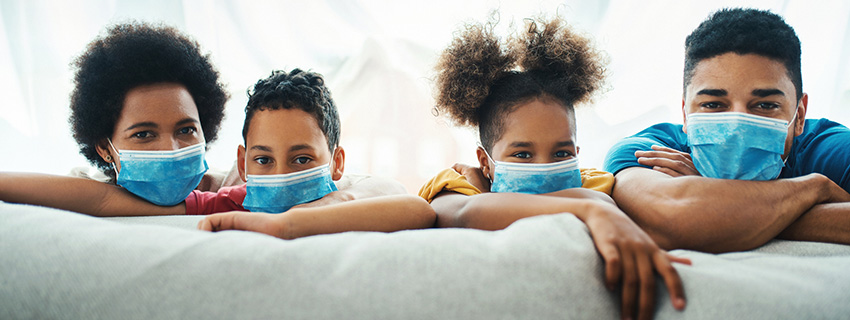 Children wearing face masks and staying at home. They are leaning over sofa and looking at the camera.