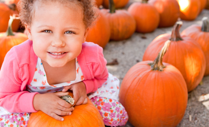 Close up of a child smiling in a pumpkin patch