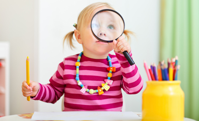 Toddler holding a magnifying glass to her eye