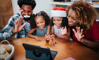Family celebrating the holidays at home and connecting with loved ones virtually.