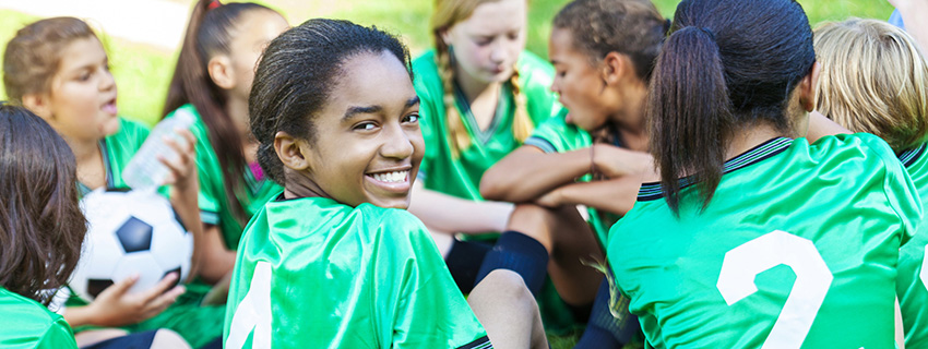 African American girl turning around and smiling at camera while sitting down with her all girls soccer team. Their uniforms are a bright green.