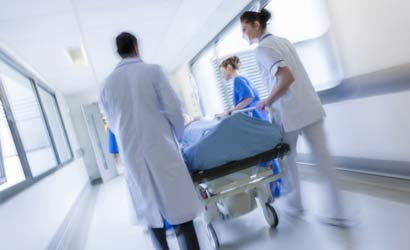 Health professionals rushing gurney through hospital hallway