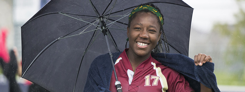 Teen Girl running from the rain with umbrella after a Game of Rugby
