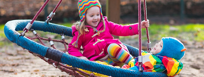 Children bundled up for winter playing outside on a swing
