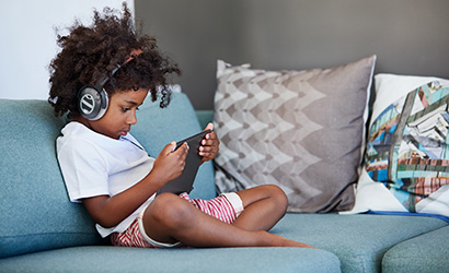 Shot of a focused young little boy browsing on a digital tablet and wearing headphones while relaxing on the couch at home