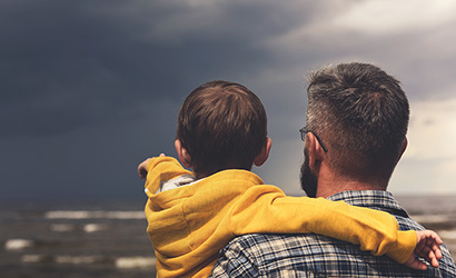 Dad and son watching a storm roll in on the beach.