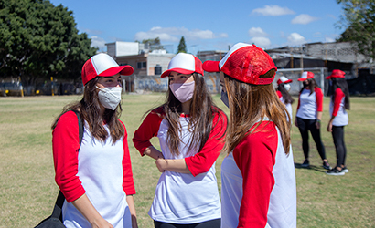 Teenage friends wearing masks during softball practice.