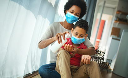 Mother and son in at home under pandemic quarantine. Mother and son sitting next to window in masks as mom puts hand sanitizer on boy's hands.