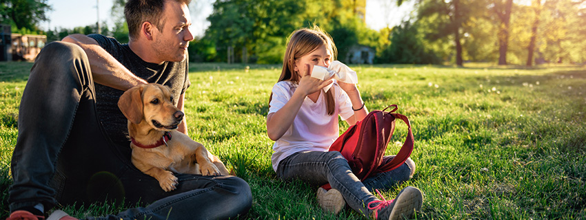 Dad outside with his dog and daughter who is holding a tissue to her nose