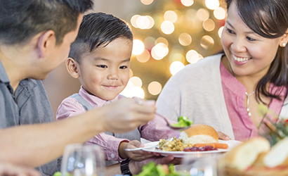 Child holding out his plate for more food during Thanksgiving