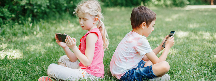 Boy and girl play games on smartphones outdoors.
