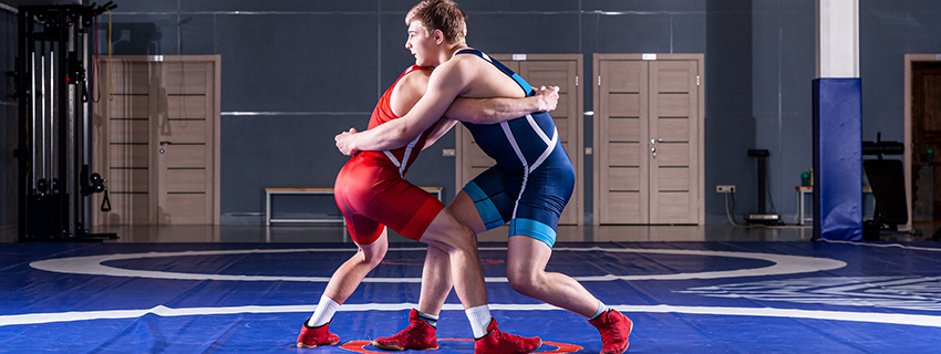 Two boys wrestling in a gym