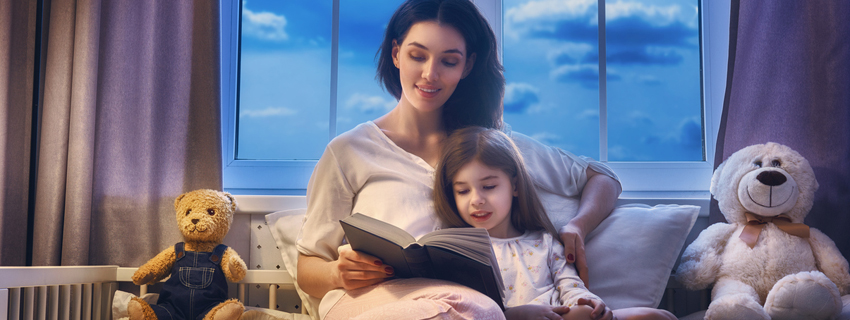 Mother reading a bedtime story to her daughter