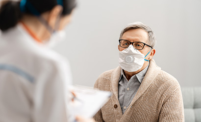 Man wearing face mask with a valve during doctor's visit