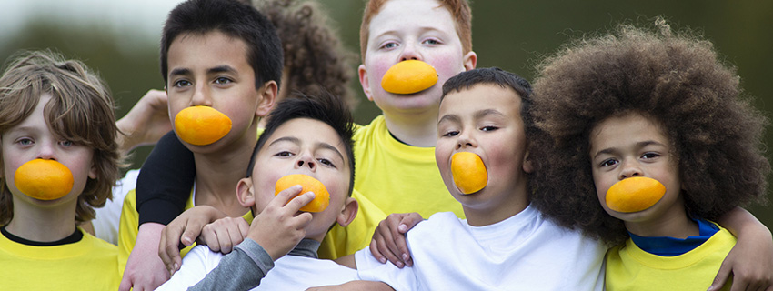Young athletes with oranges in their mouths