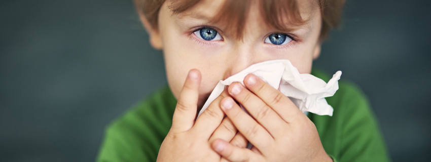Close up of a young boy holding a tissue to his nose