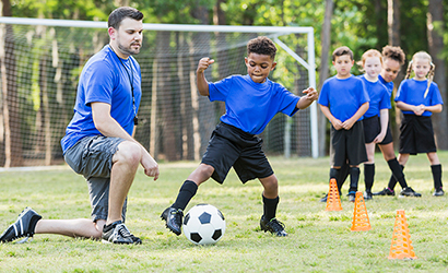 Boy running soccer drills with his coach.