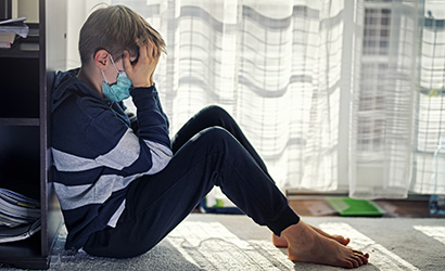 Upset boy sitting by the window, wearing surgical mask.