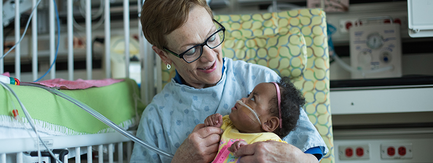 CHKD volunteer cuddler with a baby in the NICU