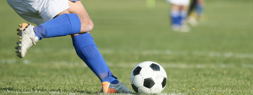 Close up of a soccer player's leg about to kick the ball