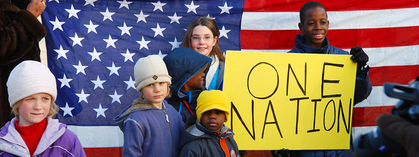 "White and black children stand with the American flag and a sign that reads ""one nation""."