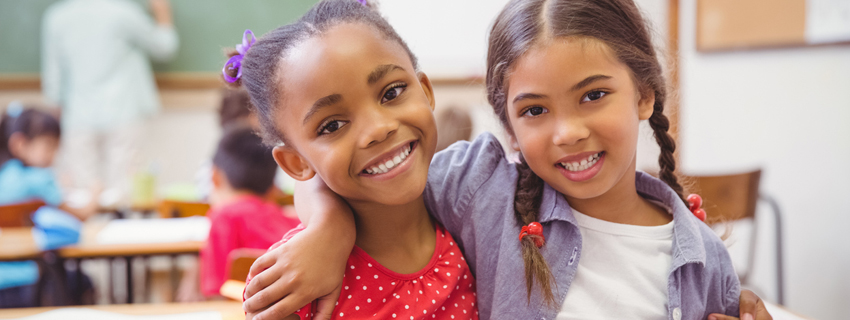 Two young girls smiling with their arms around one another in a classroom