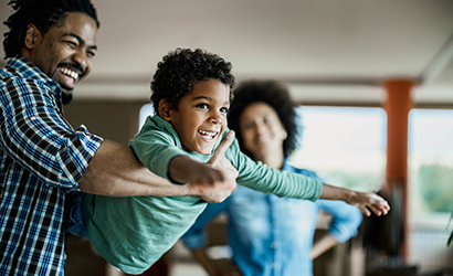 Happy African American boy having fun with his father at home.