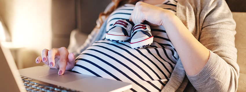 Close up of pregnant woman in bed with a laptop, holding baby shoes