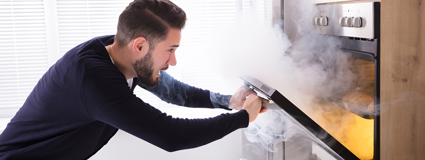 Man opening a smoky oven