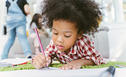 Close up of a child drawing by herself in a classroom of kids